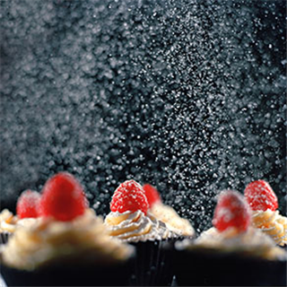 Icing sugar falling onto cupcakes with raspberries like snow photo by Roy Mehta