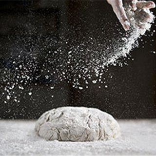 Making dough for hot cross buns with hand sprinkling flour. Photography by Roy Mehta