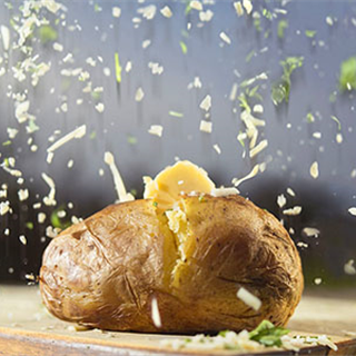Baked jacket potato with falling grated cheese and butter photo by Roy Mehta